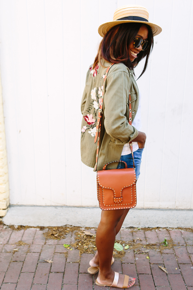 Blogger Alicia Tenise wears the Topshop Embroidered Army Jacket, Rebecca Minkoff Midnighter Top Handle Bag, and Madewell high rise denim boyshorts.