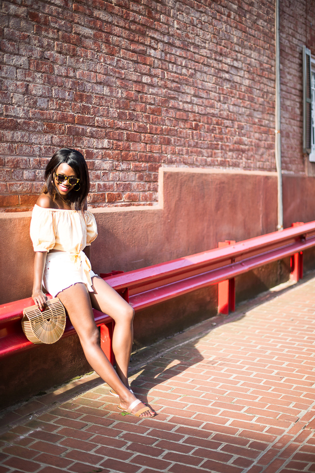 Philadelphia fashion blogger Alicia Tenise styles the Zara Orange Off the Shoulder Gingham Crop Top, Levis 501 Shorts in White, and Cult Gaia Ark Bag
