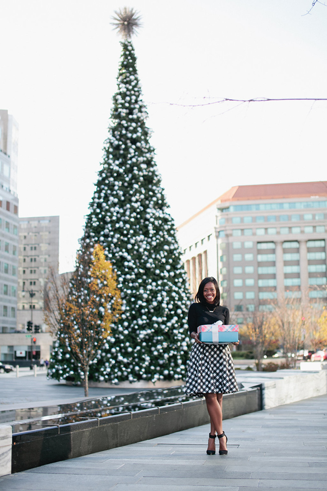 christmas outfit ideas, buffalo plaid check skirt, talbots plaid skirt, dc blogger, arlington fashion blog, citycenterdc christmas tree | Christmas in Washington D.C. by popular Washington D.C. life and style blogger, Alicia Tenise: image of woman holding some presents outside by a large Christmas tree.