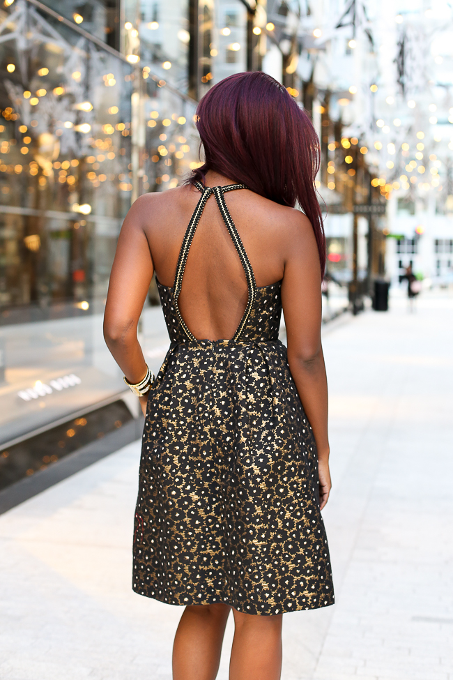Backless Dress for the Holidays| The Perfect gold holiday cocktail dress featured by top Virginia fashion blogger, Alicia Tenise: picutre of a woman wearing a Rent the Runway dress, Steve Madden sandals, Kendra Scott earrings and rings and Baublebar bracelet