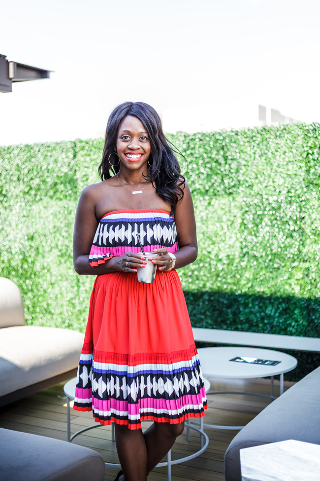 Rent the Runway Review featured by top US fashion blogger Alicia Tenise; Image of a woman wearing Kate Spade Geo Border Pleated Dress.