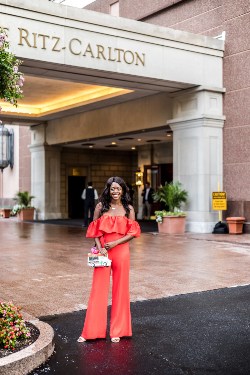 Rent the Runway Review featured by top US fashion blogger Alicia Tenise; Image of a woman wearing coral jumpsuit.