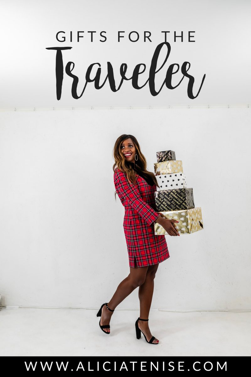 Blogger Alicia Tenise shares her favorite gift picks for travelers - Holiday Gift Guide: Travel Gift Ideas by Washington DC travel blogger Alicia Tenise | Holiday Gift Guide: 17 Gift Ideas for People who Travel by popular life and style blogger, Alicia Tenise: image of a woman wearing a red and green plaid dress and holding a stack of wrapped presents.