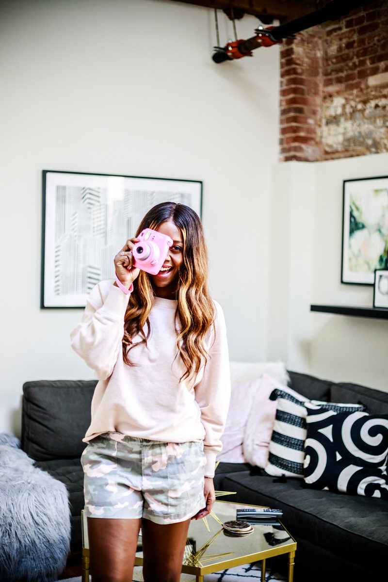 Instax Fuji in Pink - The Best Camera Gear Under $100 featured by popular Virginia blogger Alicia Tenise | Best Camera Gear by popular DC lifestyle blogger, Alicia Tenise: image of a woman holding a pink Instax Fuji camera.