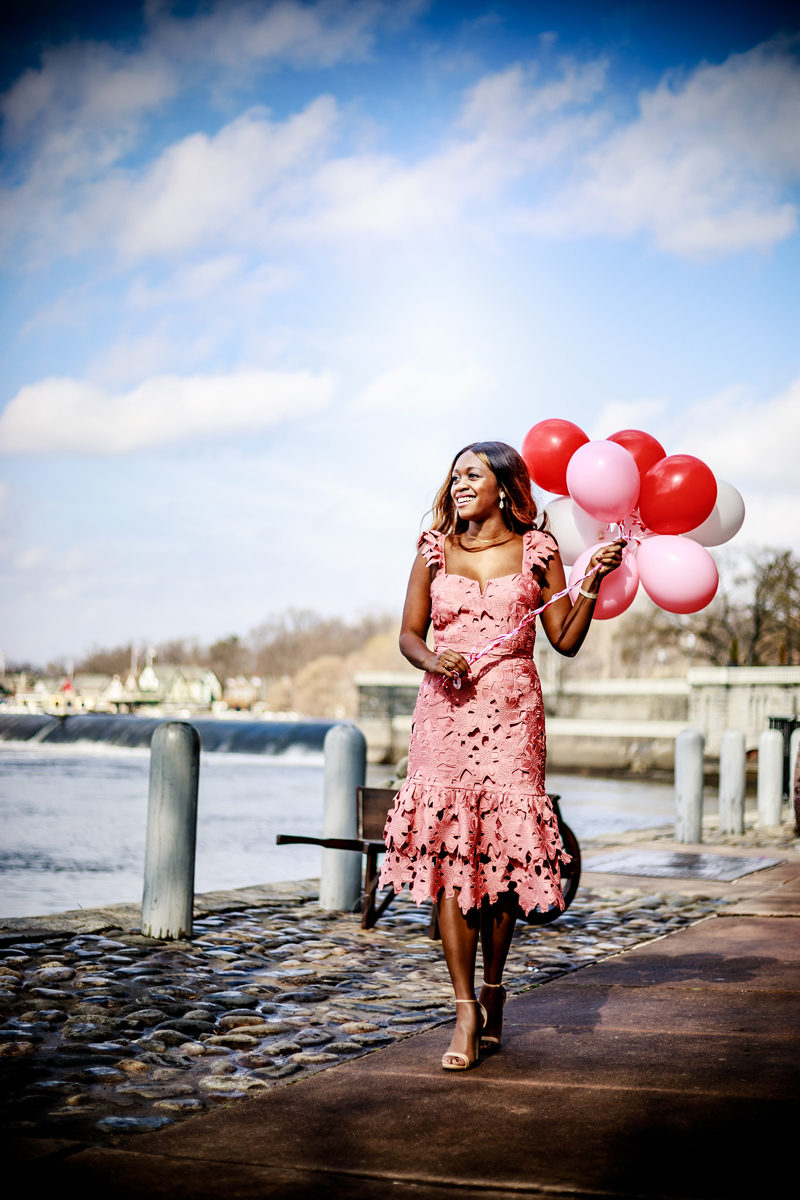 Rent the Runway Review featured by top US fashion blogger Alicia Tenise; Image of a woman wearing pink lace dress and carrying balloons.