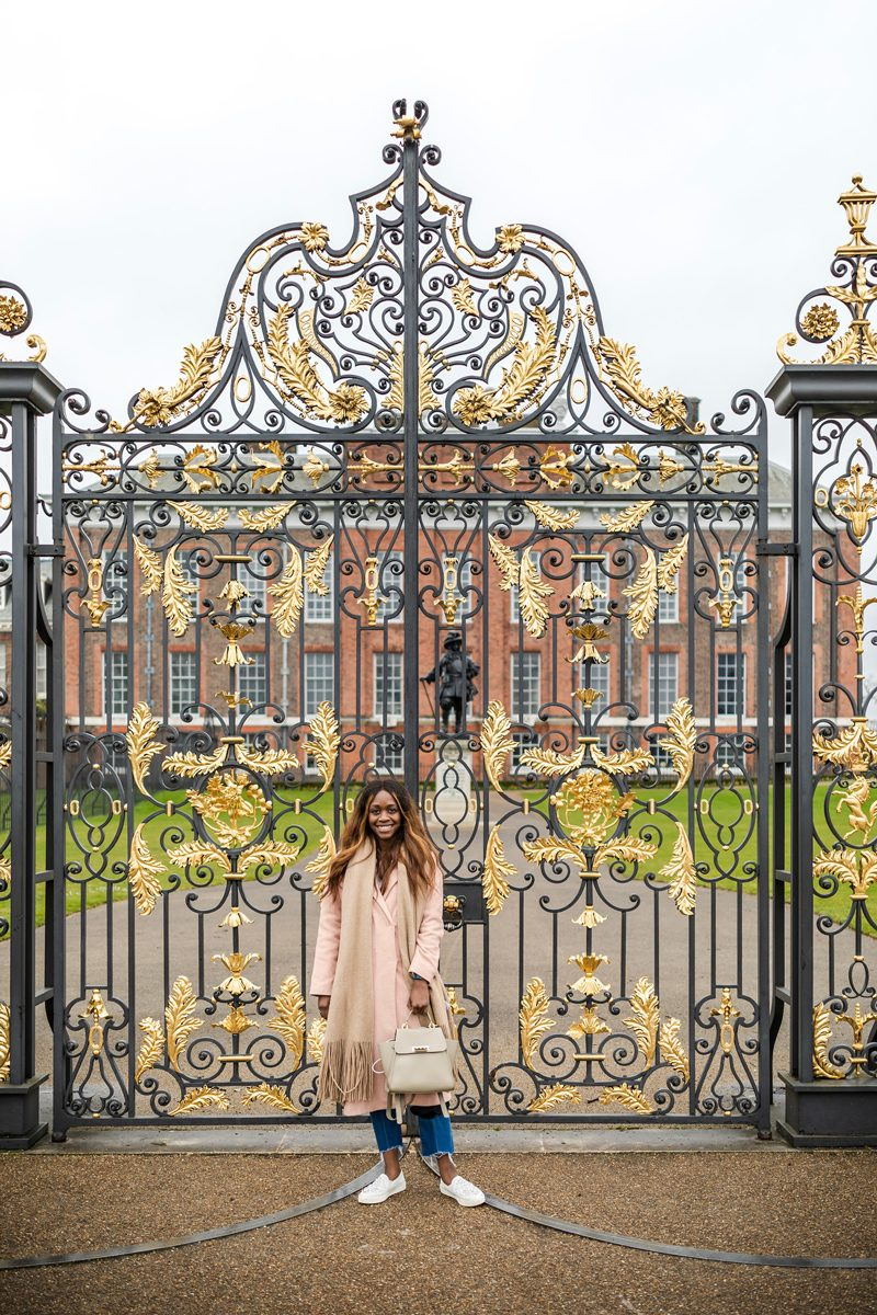 Virtual Tour Websites by popular D.C. travel blogger, Alicia Tenise: image of a woman standing in front of the gates of Buckingham Palace.
