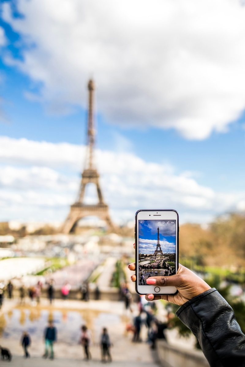 Paris Visitor's Guide | Virtual Tour Websites by popular D.C. travel blogger, Alicia Tenise: image of a woman in Paris, France taking a picture of the Eiffel Tower with her smart phone.