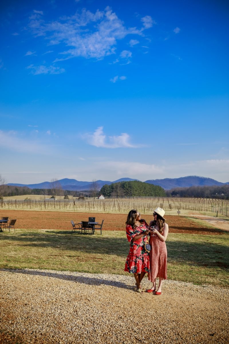 Afton Mountain Vineyards - 10 Wineries in Virginia You Need to Visit featured by popular Virginia travel blogger, Alicia Tenise |Virginia Wineries by popular D.C. travel blogger, Alicia Tenise: image of Alicia Tenise and her friend standing outside at a vineyard.