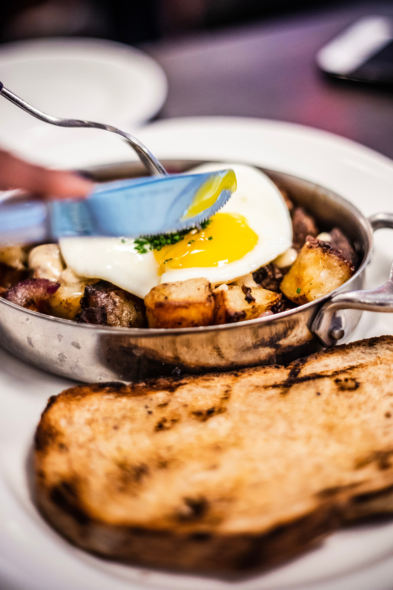 Le Politique Brunch | The Ultimate Guide of Things to Do in Austin TX featured by top Virginia travel blog Alicia Tenise | Things to do in Austin by popular LA travel blogger, Alicia Tenise: image of someone cutting into a sunny side up egg on some cooked potatoes.