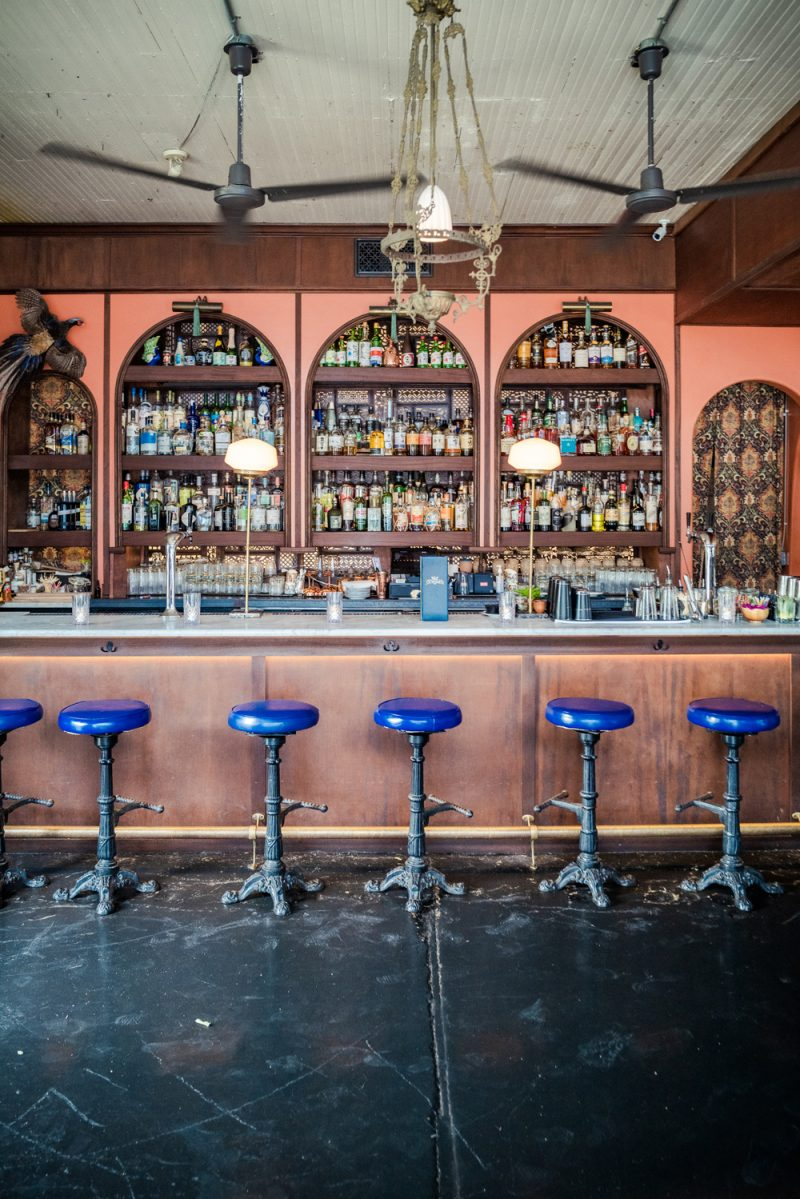 Ah Sing Den Austin | Things to do in Austin by popular LA travel blogger, Alicia Tenise: image of a bar with blue bar stools.