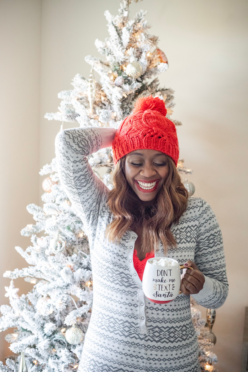 Aerie Pajama Jumpsuit  | Aerie Holiday PJs featured by top DC fashion blogger, Alicia Tenise: image of a woman wearing plaid holiday pjs and a red pompom beanie in front of her Christmas tree