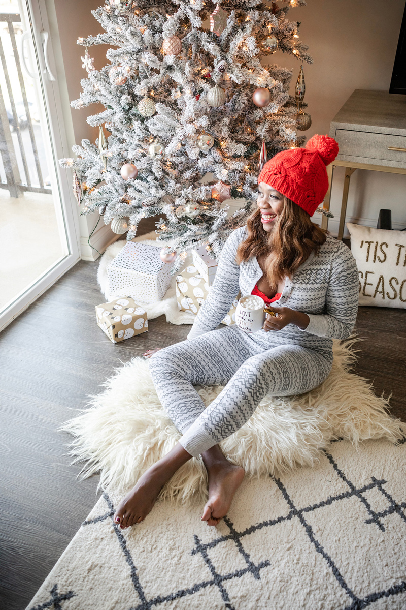 Holiday Onesie PJs | Aerie Holiday PJs featured by top DC fashion blogger, Alicia Tenise: image of a woman wearing plaid holiday pjs and a red pompom beanie in front of her Christmas tree
