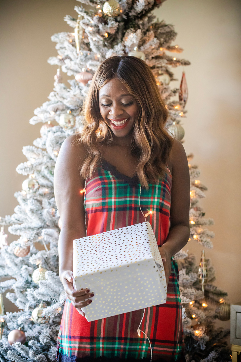 Plaid Holiday Pajamas | Aerie Holiday PJs featured by top DC fashion blogger, Alicia Tenise: image of a woman wearing plaid holiday pjs and holding a Christmas gift.