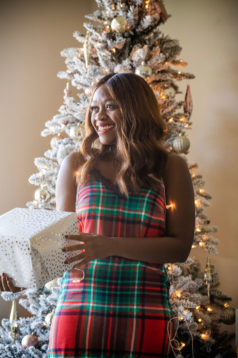 Aerie Plaid Nightie | Aerie Holiday PJs featured by top DC fashion blogger, Alicia Tenise: image of a woman wearing plaid holiday pjs and holding a Christmas gift.