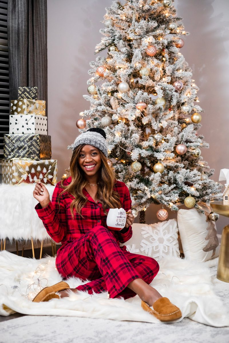Soma Embraceable Long Sleeve Notch Collar Pajama Top Peace And Joy Plaid Red | The Best Christmas PJs by popular Washington DC fashion blogger, Alicia Tenise: image of a woman sitting next her Christmas tree and wearing a Soma Embraceable Long Sleeve Notch Collar Pajama Top Peace And Joy Plaid Red, Soma EMBRACEABLE Pajama Pants Peace And Joy Plaid Red, and Koolabura Women's Lezly.