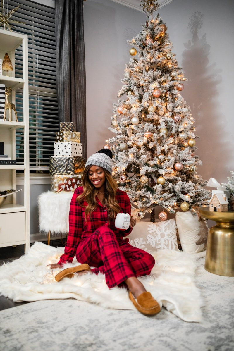 Plaid Holiday Pajamas | Soma Holiday PJs featured by top DC fashion blogger, Alicia Tenise: image of a woman wearing plaid holiday pjs and holding a Christmas mug. | The Best Christmas PJs by popular Washington DC fashion blogger, Alicia Tenise: image of a woman sitting next her Christmas tree and wearing a beaning and red and black flannel pjs.
