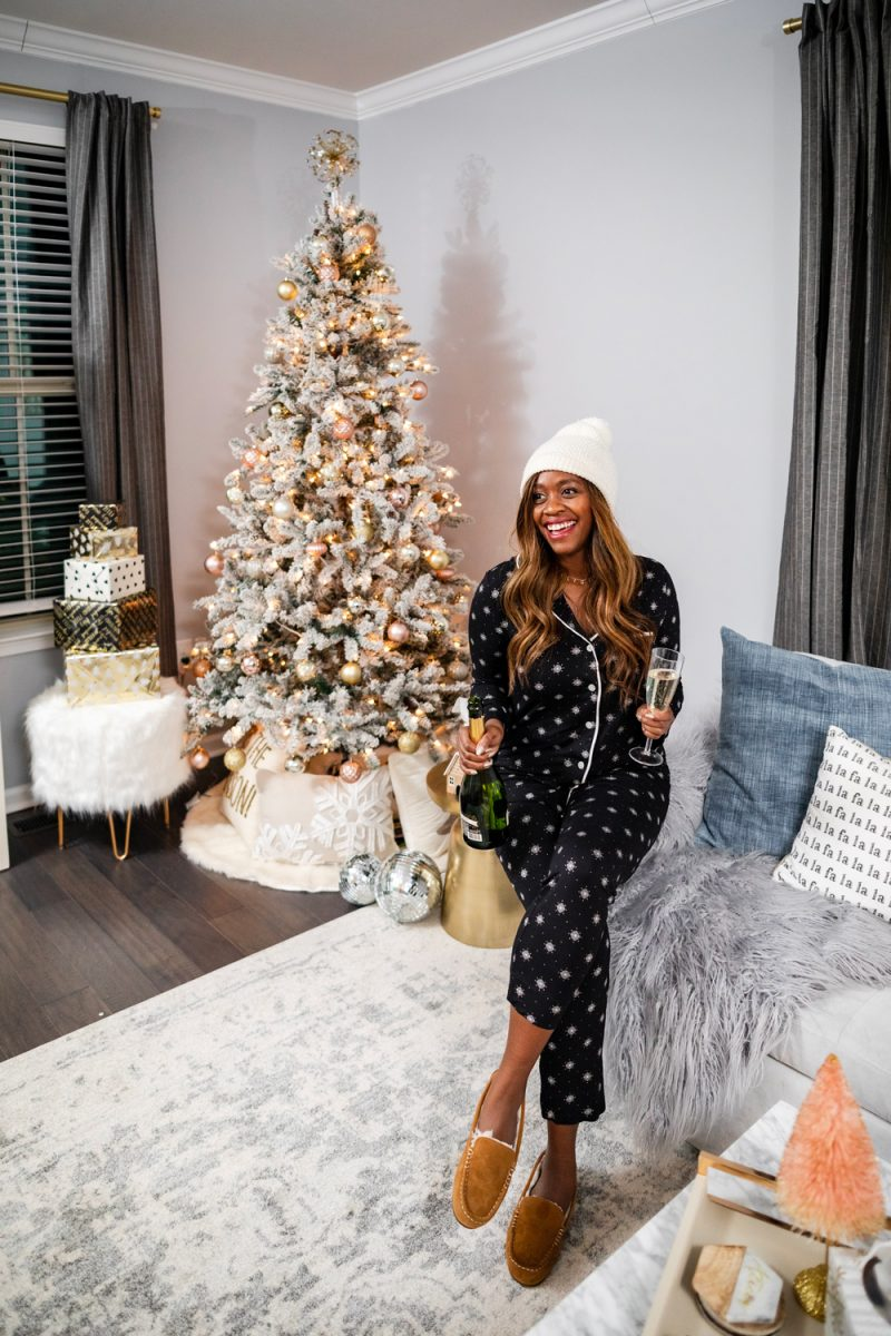 Holiday PJs | Soma Cool Nights Holiday PJs featured by top DC fashion blogger, Alicia Tenise: image of a woman wearing snowflake holiday pjs and a white pompom beanie in front of her Christmas tree | The Best Christmas PJs by popular Washington DC fashion blogger, Alicia Tenise: image of a woman sitting next her Christmas tree and wearing a Soma Cool Nights Long Sleeve Grosgrain Trim Notch Collar Pajama Top Snowflakes, Soma Cool Nights Grosgrain Trim Ankle Pajama Pants Snowflakes, KoolaBura Women's Lezly, and Nordstrom TopShop Cable Pom Beanie.