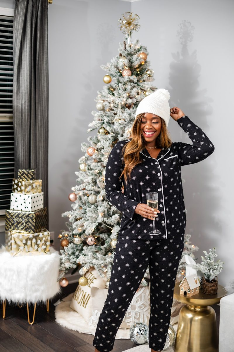 Soma Cool Nights Long Sleeve Grosgrain Trim Notch Collar Pajama Snowflakes Black | The Best Christmas PJs by popular Washington DC fashion blogger, Alicia Tenise: image of a woman standing next her Christmas tree and wearing a Soma Cool Nights Long Sleeve Grosgrain Trim Notch Collar Pajama Top Snowflakes, Soma Cool Nights Grosgrain Trim Ankle Pajama Pants Snowflakes, KoolaBura Women's Lezly, and Nordstrom TopShop Cable Pom Beanie.