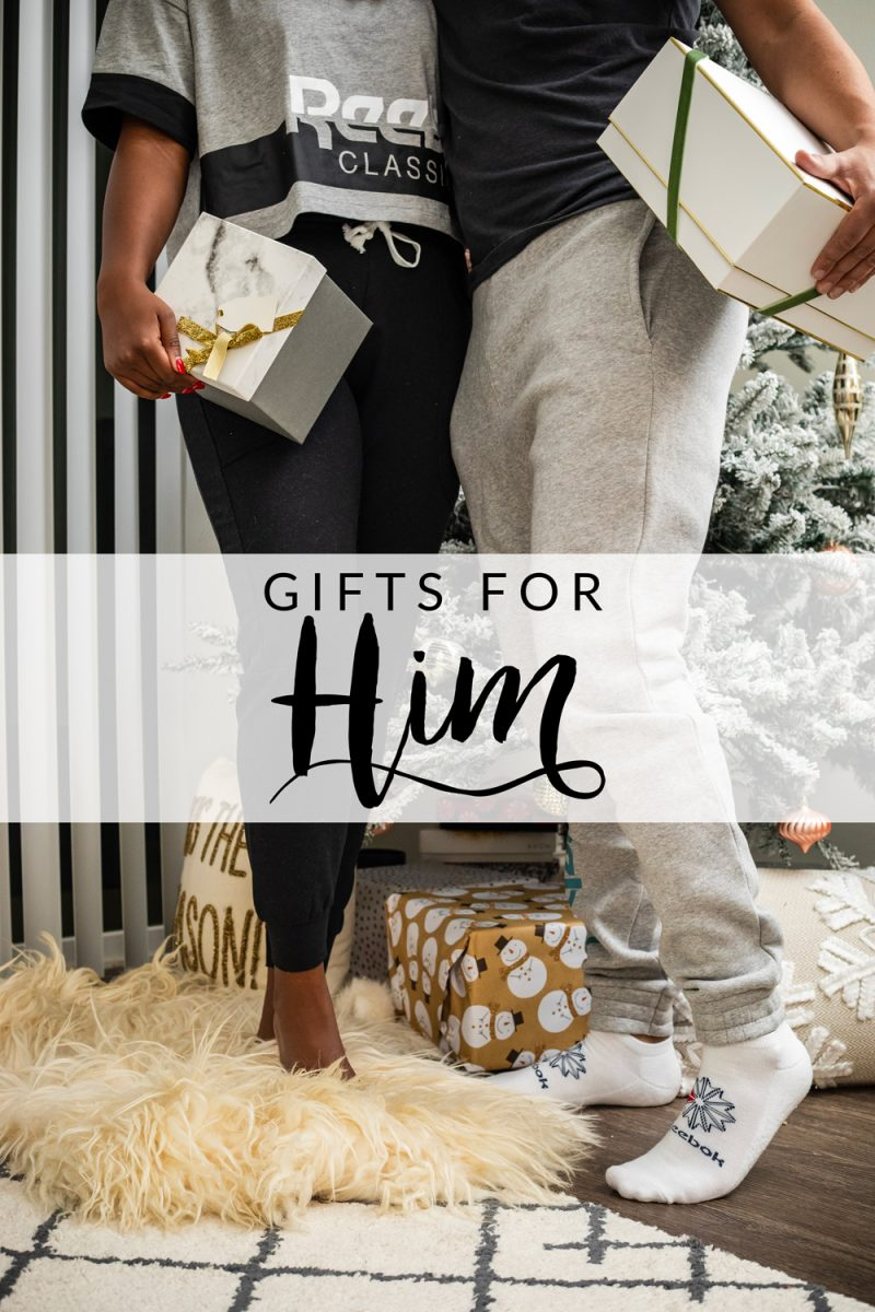 13 Unique Gifts for Him by popular Washington D.C. life and style blogger, Alicia Tenise: image of a man and woman standing next to each other by a Christmas tree and holding presents.