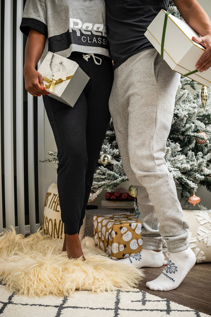 Stay At Home Date Ideas by popular DC lifestyle blogger, Alicia Tenise: image of a man and woman standing next to each other and holding presents.