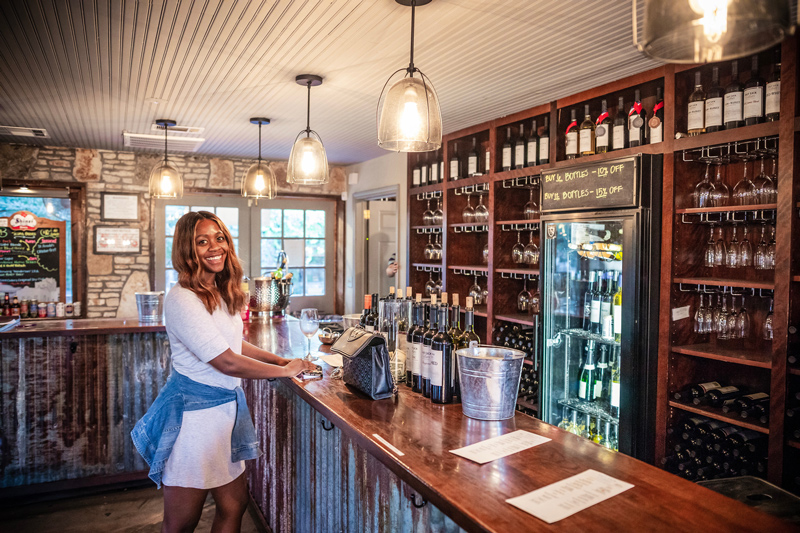 Wine Tasting at Salt Lick Cellars | Salt Lick Cellars | The Best Wineries in Texas Hill Country featured by top US travel blogger, Alicia Tenise: Image of woman at the salt lick cellars at the bar
