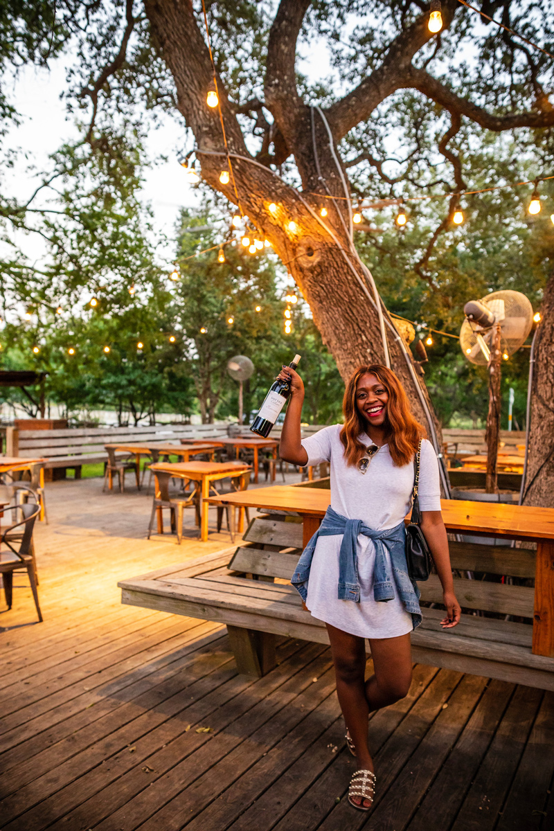 Salt Lick Cellars Texas Wine | Salt Lick Cellars | The Best Wineries in Texas Hill Country featured by top US travel blogger, Alicia Tenise: Image of woman at the Salt Lick Cellars with a bottle of wine