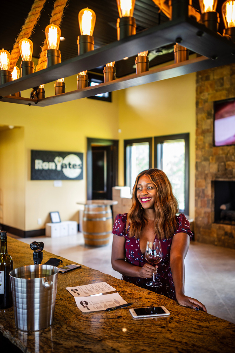 Ron Yates Winery | Salt Lick Cellars | The Best Wineries in Texas Hill Country featured by top US travel blogger, Alicia Tenise: Image of woman at Lewis Wines