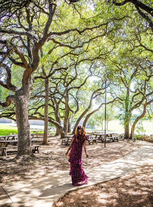 Texas Hill Country Wine Guide | Salt Lick Cellars | The Best Wineries in Texas Hill Country featured by top US travel blogger, Alicia Tenise: Image of a woman in the woods