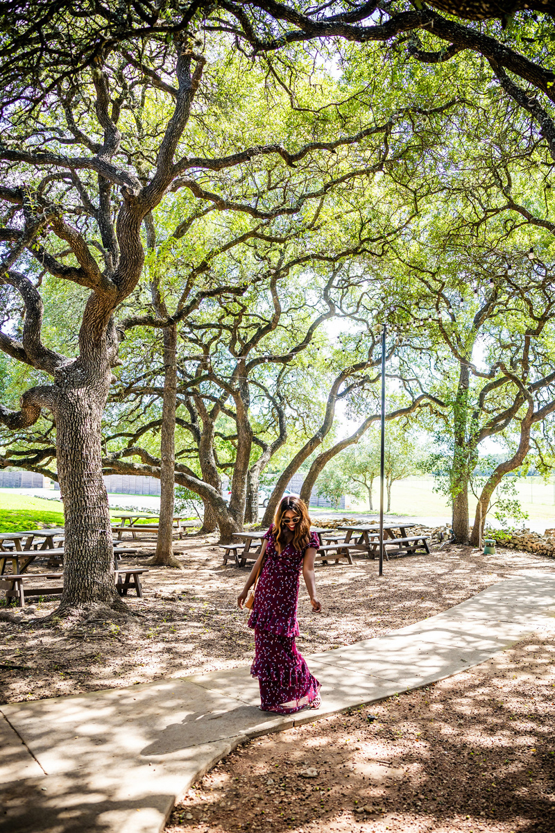 Texas Hill Country Wine Guide | Salt Lick Cellars | The Best Wineries in Texas Hill Country featured by top US travel blogger, Alicia Tenise: Image of a woman in the woods | The Most Popular Blog Posts of 2019 by popular Washington DC life and style blogger, Alicia Tenise: image of a woman walking outside.