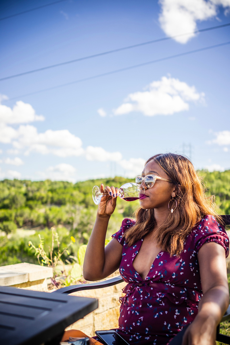 The Best Wineries in Texas Hill Country featured by top US travel blogger, Alicia Tenise: image of a woman drinking wine in Texas hill country