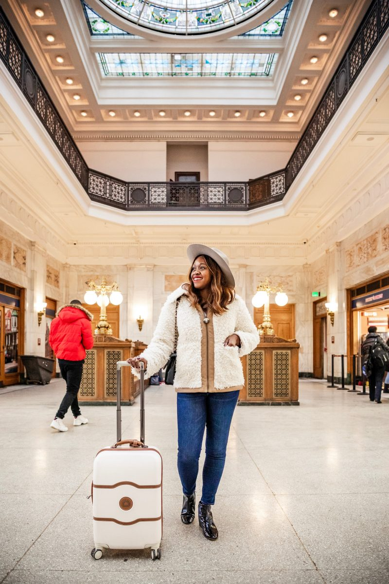 My Travel Bucket List for 2019 featured by top US travel blogger Alicia Tenise; Image of a woman wearing And Other Stories Faux Shearling Workwear Jacket, Delsey Chatelet Plus 21 Carry-On Hardside Spinner Suitcase