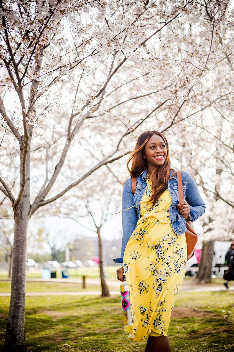 Best Things to Do in D.C. in the Spring featured by top DC blogger Alicia Tenise; Image of a woman wearing a yellow floral dress and denim jacket.