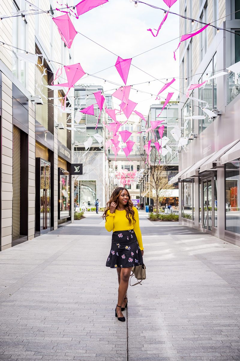 Best Things to Do in D.C. in the Spring featured by top DC blogger Alicia Tenise; Image of a woman wearing a yellow sweater and floral skirt.