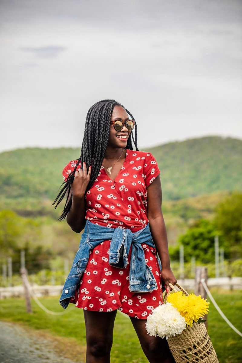How to wear a floral romper featured by top US fashion blogger, Alicia Tenise: image of a woman wearing a LOFT denim jacket, a LOFT wrap floral romper, LOFT loafer slides and LOFT sunglasses