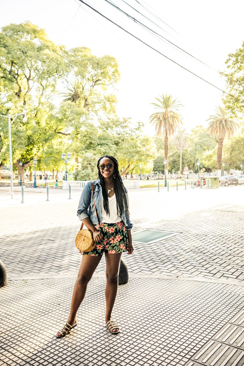 Mendoza Travel Guide featured by top US travel blogger Alicia Tenise; Image of a woman wearing floral shorts and a denim jacket.
