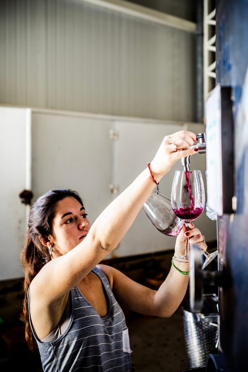 Wine Tasting in Mendoza featured by top US travel blogger Alicia Tenise; Image of a woman pouring wine.