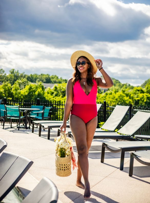 How to spend the perfect Memorial Day Weekend staycation featured by top US travel blogger, Alicia Tenise: image of a woman wearing a color block one piece swimsuit by the pool