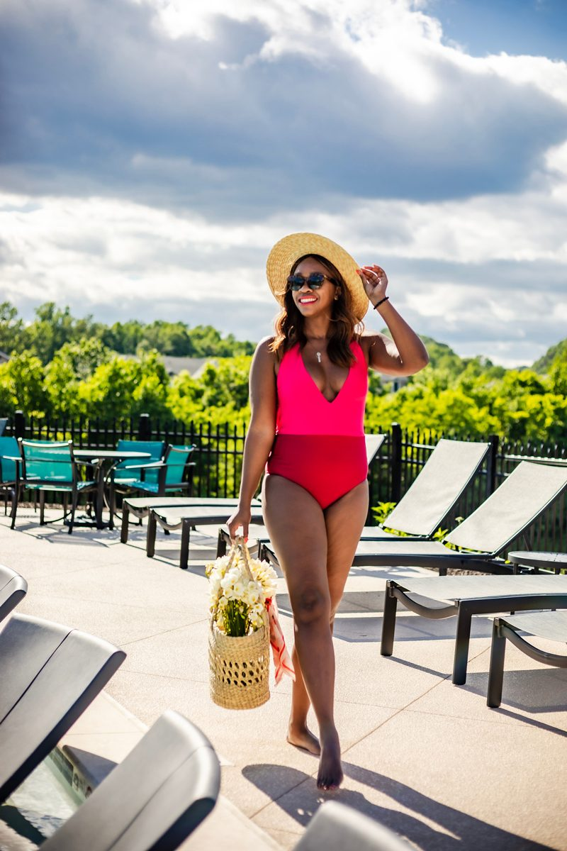 How to spend the perfect Memorial Day Weekend staycation featured by top US travel blogger, Alicia Tenise: image of a woman wearing a one piece swimsuit by the pool