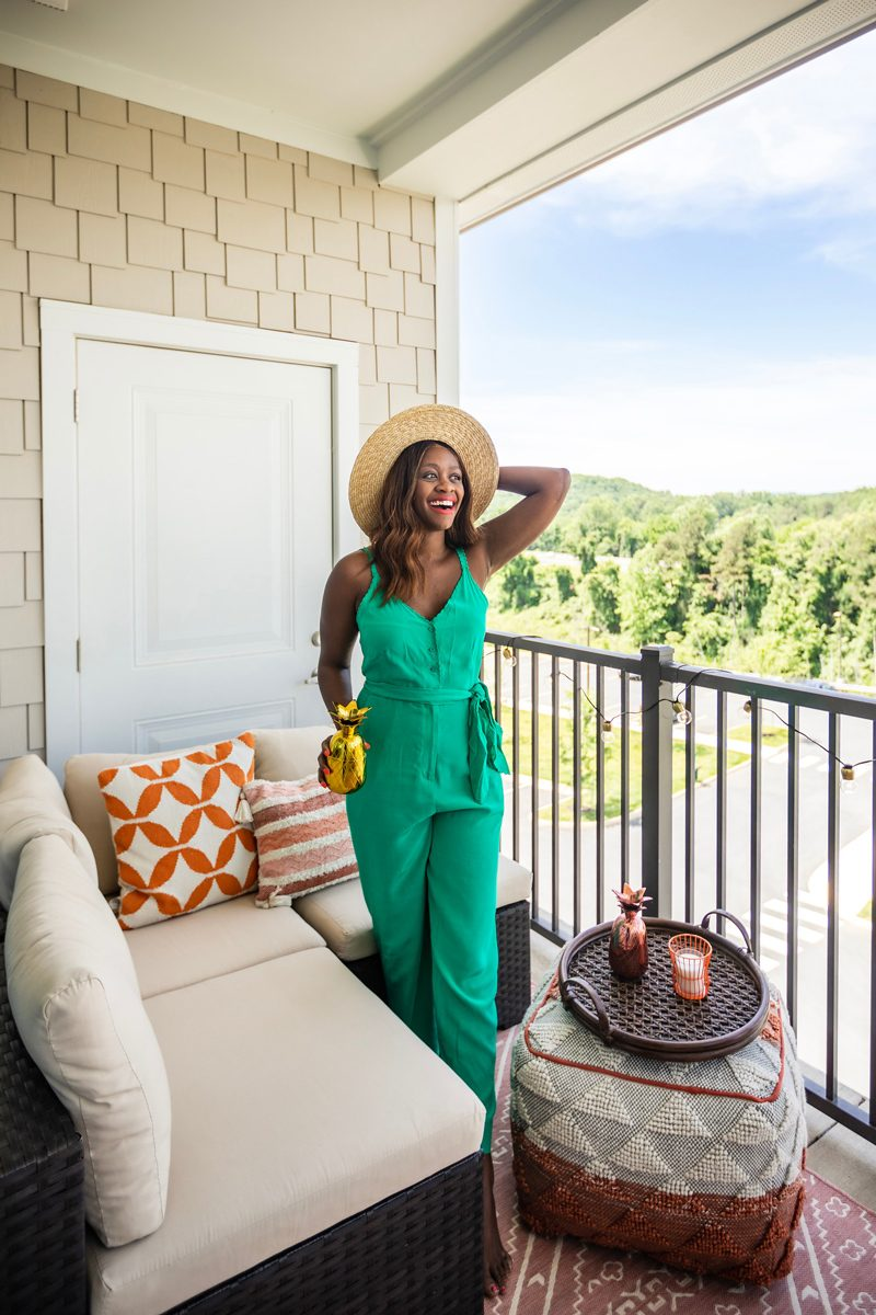 Balcony Decorating Ideas featured by top US life and style blogger Alicia Tenise; Image of a woman wearing a teal jumpsuit.