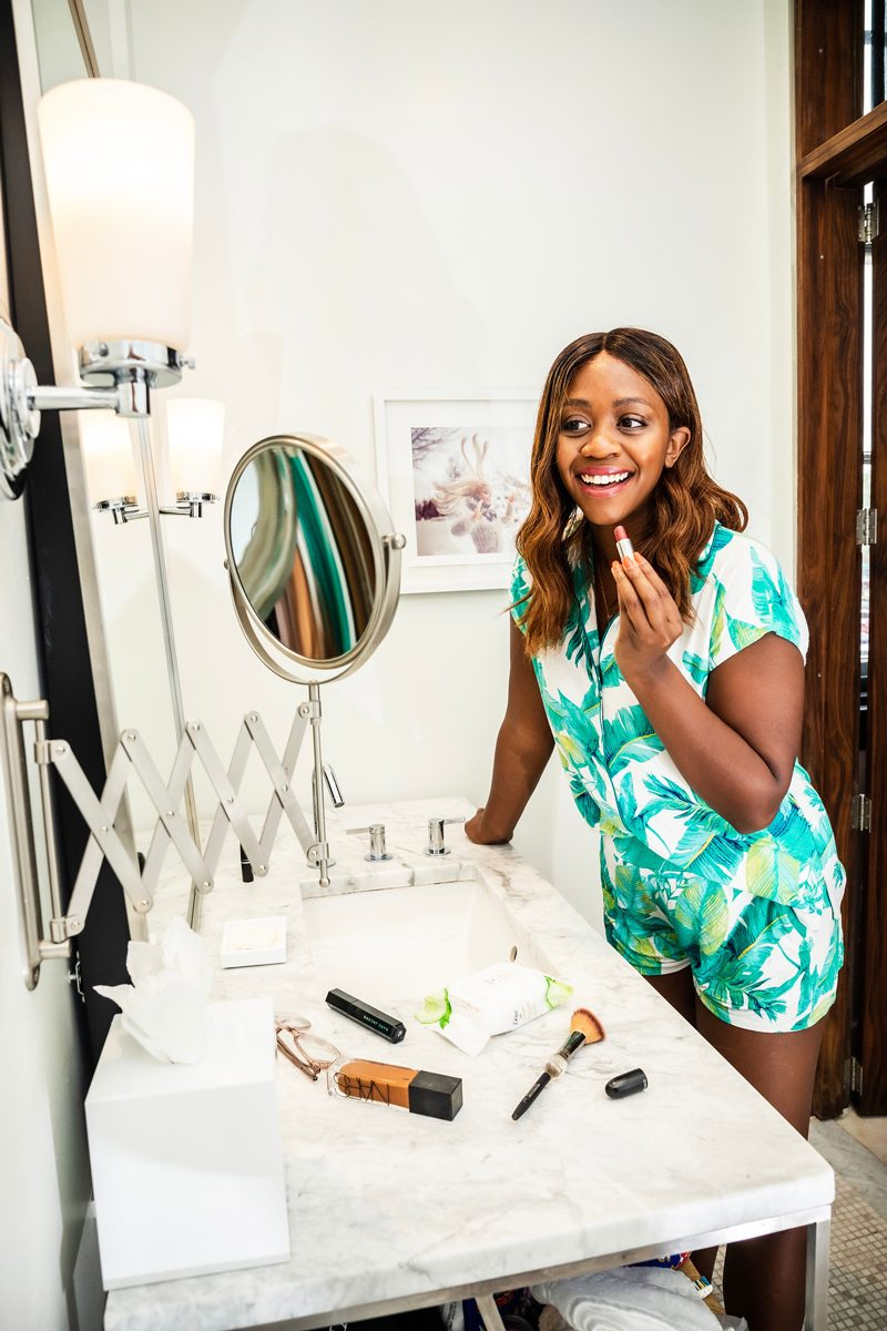 The Bloom Salon featured by top US beauty blogger Alicia Tenise; Image of a woman putting on her makeup.