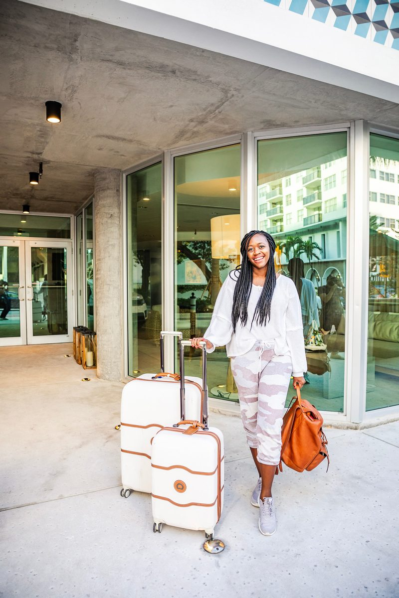How to Avoid Travel Burnout by popular DC travel blogger Alicia Tenise: image of a woman standing outside an airport with white luggage, and wearing grey sneakers, grey camo sweatpants, and a grey sweater.