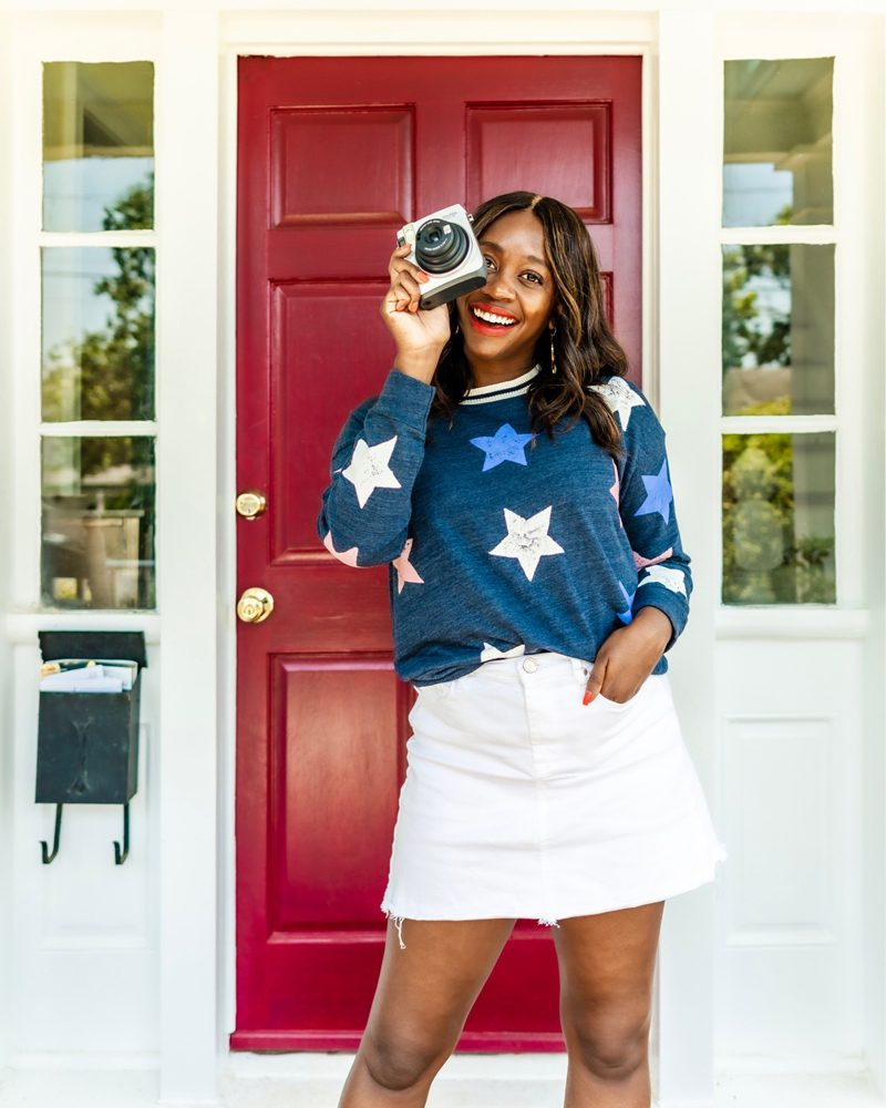 Splendid Liberty Active Star-Print Sweatshirt, White Denim Mini Skirt | Last Minute 4th of July Outfit Ideas by popular Washington DC fashion blogger, Alicia Tenise: image of a woman standing outside in front of read door and holding a white Polaroid camera.  Woman is wearing a Splendid Liberty Active sweater and white Blank Denim miniskirt.
