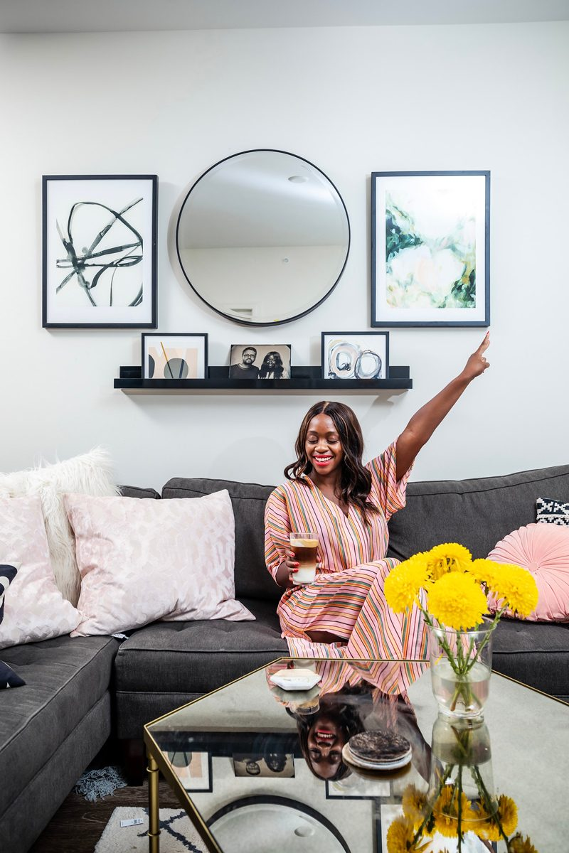 And Other Stories Striped Cotton Midi Dress | 5 Reasons Why I Don't Like Working From Home by popular lifestyle blogger, Alicia Tenise: image of a woman sitting on her grey sectional couch and holding a cup of iced coffee.