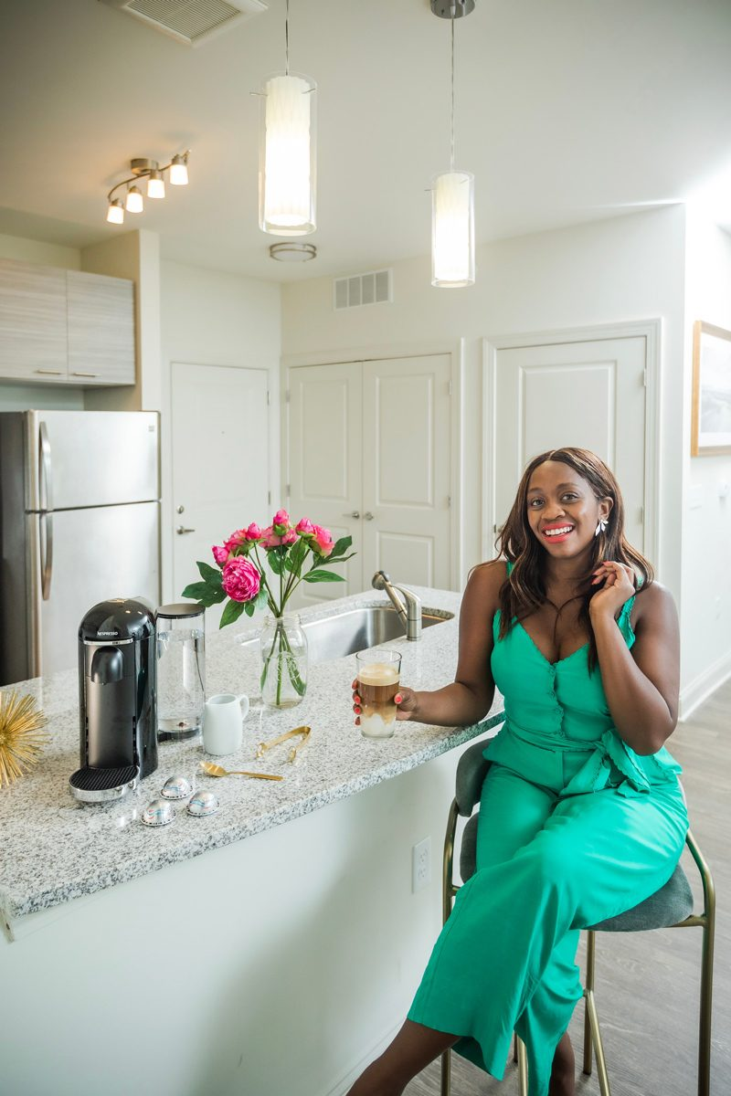 And Other Stories Belted Scallop Edge Jumpsuit, Nespresso VertuoPlus Deluxe Coffee and Espresso Maker | 5 Reasons Why I Don't Like Working From Home by popular lifestyle blogger, Alicia Tenise: image of a woman sitting in a stool at her kitchen countertop and holding a cop of iced coffee.