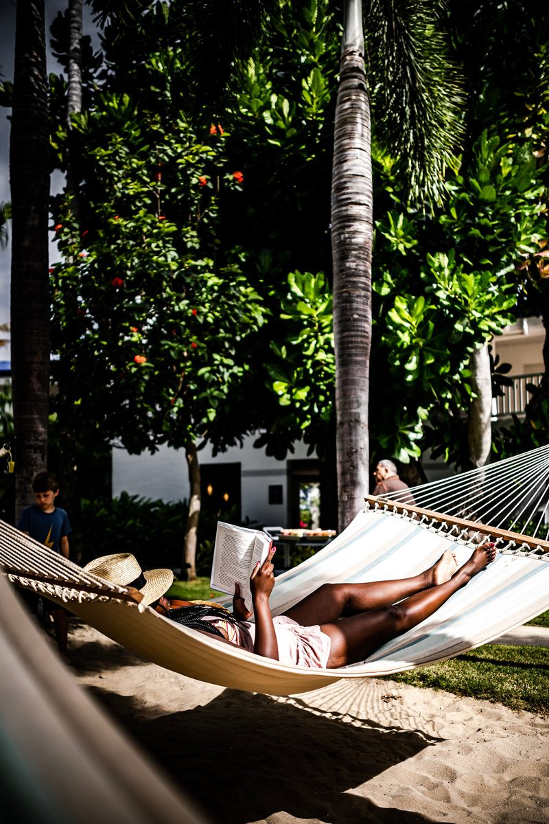 Why I Didn't Travel That Much This Summer + My Fall Travel Bucket List Plans by popular Washington D.C. travel blogger, Alicia Tenise: image of a woman sitting in a hammock and reading a book.