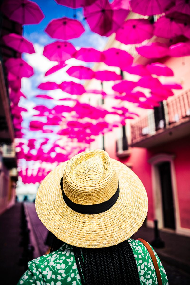Umbrella Street in Old San Juan | How to be an Ally by popular D.C. lifestyle blogger, Alicia Tenise: image of Alicia Tenise wearing a straw fedora hat and walking down Umbrella Street in Old San Juan.