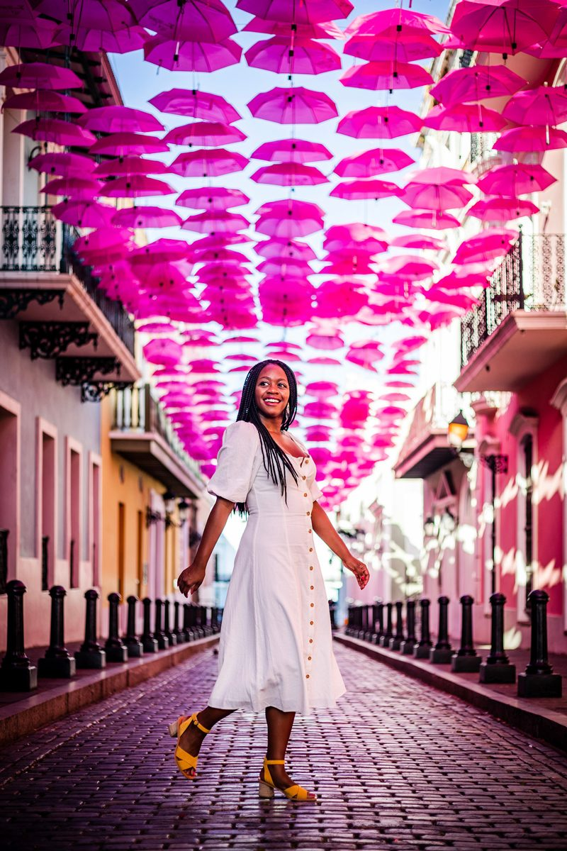 48 Hours in Old San Juan: A Travel Guide by popular Washington D.C. travel blogger, Alicia Tenise: image of a woman walking under Colorful Umbrellas on Fortaleza Street - Old San Juan Puerto Rico