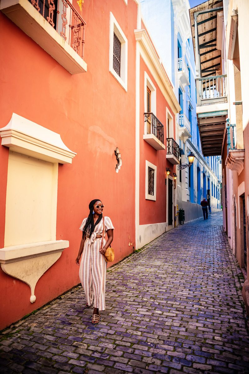 48 Hours in Old San Juan: A Travel Guide by popular Washington D.C. travel blogger, Alicia Tenise: image of a woman walking down Colorful Streets in Old San Juan