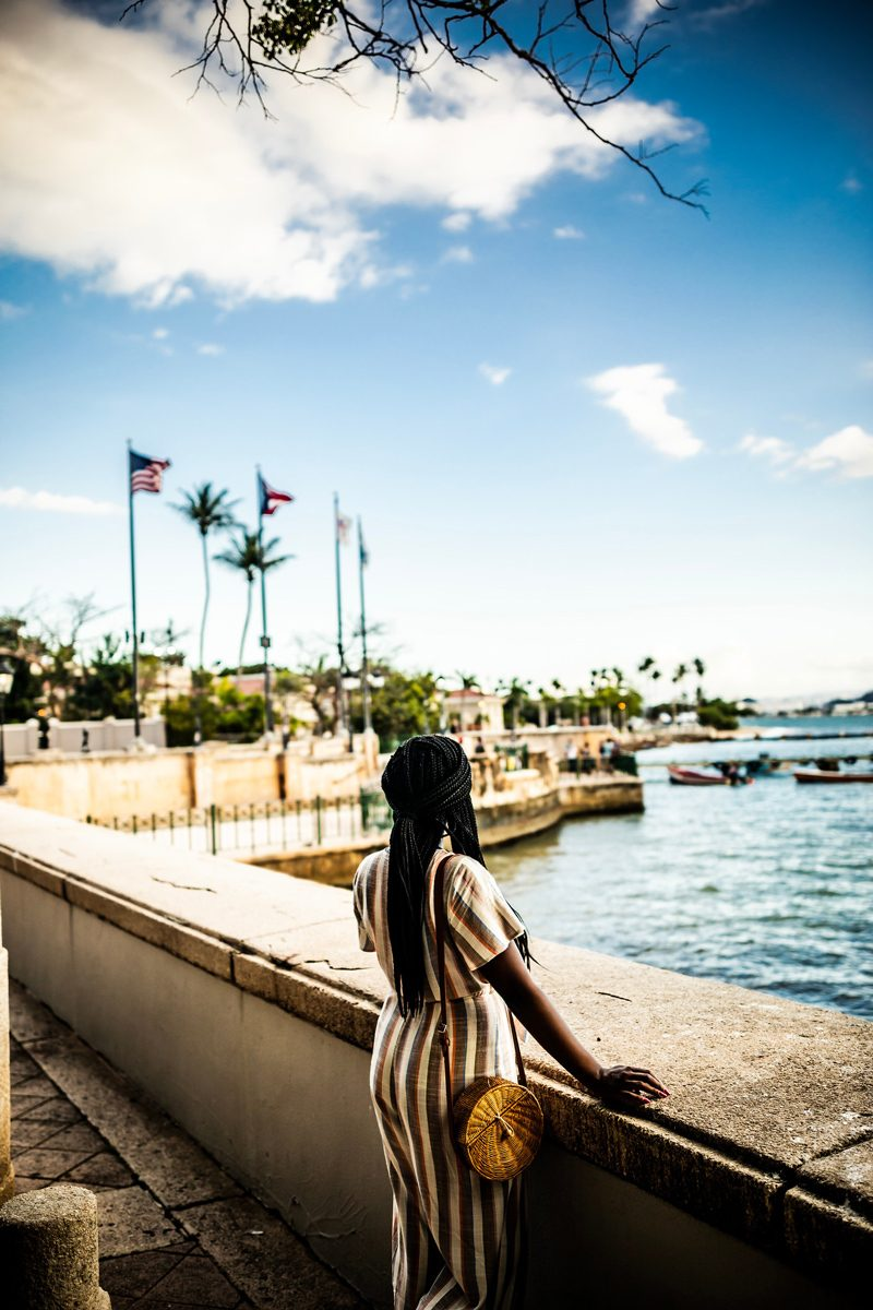 Paseo la Princesa Old San Juan | Virtual Tour Websites by popular D.C. travel blogger, Alicia Tenise: image of a woman in Old San Juan Puerto Rico looking out at the ocean.