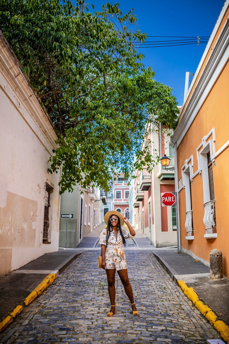 48 Hours in Old San Juan: A Travel Guide by popular Washington D.C. travel blogger, Alicia Tenise: image of a woman standing on a cobblestone street surrounded by colorful buildings in Old San Juan, Puerto Rico.
